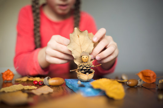 autumn craft with kids. children's cute boat with man made of natural materials. process of creating