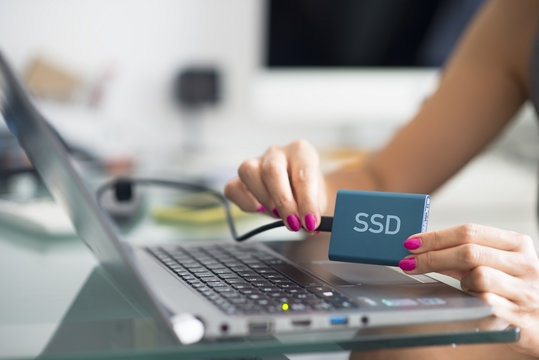 Woman using solid state drive (SSD) at personal laptop, modern equipment which provides better performance and reliability over an HDD