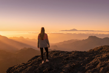 Fototapeten Dunkelbraun Happy young woman standing and enjoying life at sunset in mountains - gran canaria, spain