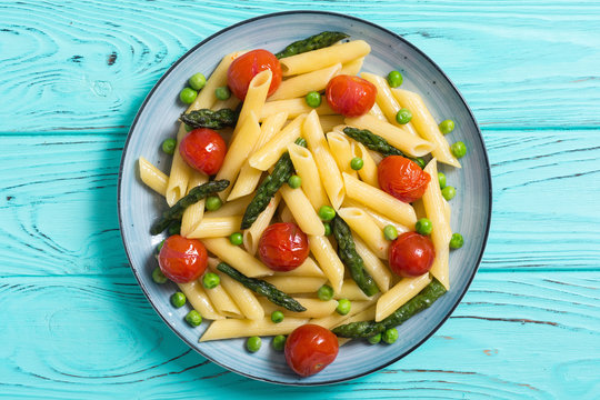 Penne pasta salad with asparagus , tomatoes and peas