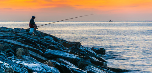 Angler fishing on the sea shore at sunrise