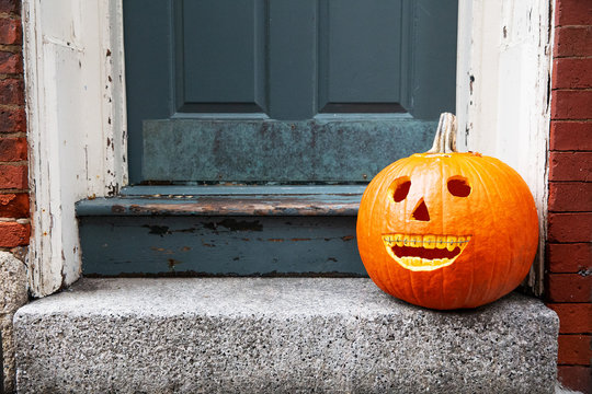 funny Halloween pumpkin on the doorstep. smiling pumpkin with braces. the concept of dentist office. copy space for your text