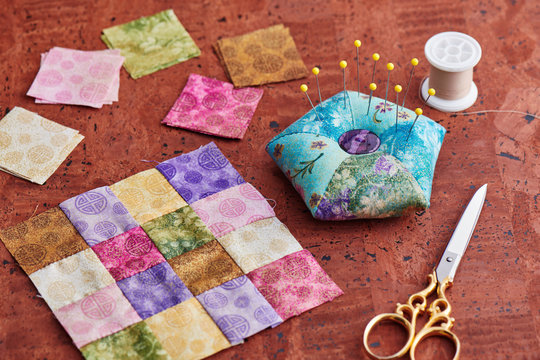 Quilting block from bright square pieces of fabrics, pin cushion, scissors, spool of thread
