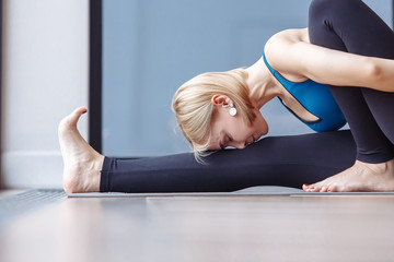 Healthy slim young girl doing marichiasana sitting on the rug on the floor in the hall during yoga. The concept of strengthening the abdominal organs