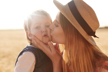 Outdoor picture of loving caring woman with straw hat on head kissing her little daughter, touching her face with hands, posing over wheat field background. Little kid looking directly at camera.