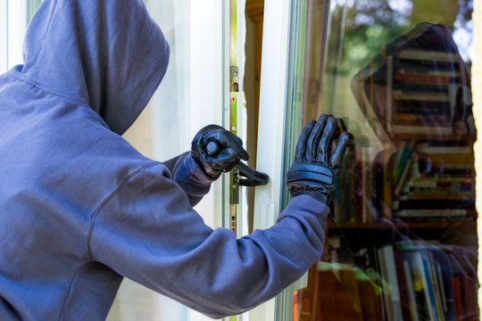 A burglar tries to break into a house in bright daylight. Concept crime.