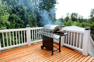 Barbecue grill cooking with visual smoke in open outdoor deck during summer day Wall mural