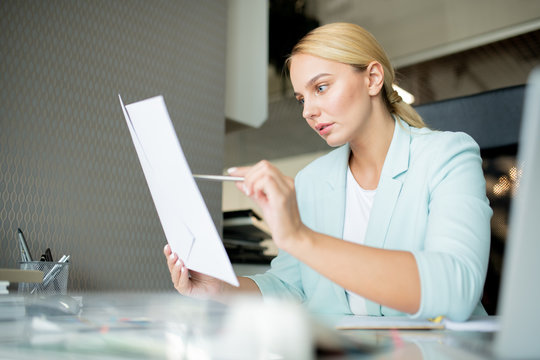 Young manager or banker pointing at financial paper while reading it