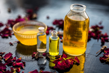 Close up of castor oil, tea tree oil, and some coconut oil in bottles on the wooden surface along with some raw honey and rose petals also present on the surface.
