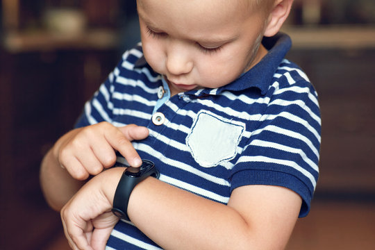 Cute little blond boy with blue eyes points out to digital fitness tracker on his wrist. Serious expression, strong emotions, children computerization concept. Indoors, dark background, copy space.