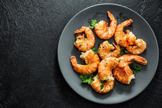 Grilled shrimps on plate on dark background