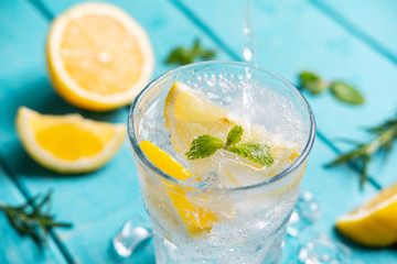 Refreshing lemonade in glass with lemon on wooden table