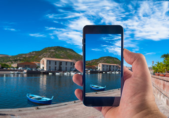 Hand taking picture with a smartphone in the village of Bosa, in Sardinia, in summer
