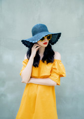 Young woman with hat wearing sunglasses and dress