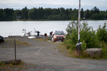An emergency services boat carrying wreckage parts arrives at a harbour near the site, where a small sports aircraft with nine people on board has crashed at Ume river outside Umea