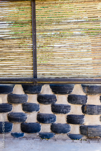 Wall made from old tyres and wooden branches at a school for