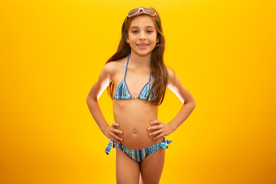 Child wearing bikini on yellow background. Concept of summer, beach and pool.