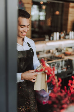 Handsome barman wiping glass with cleaning cloth