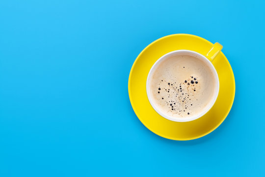 Yellow coffee cup over blue background
