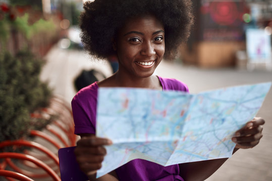 Smiling afro-american woman holding map in hands