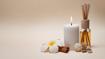 Beautiful spa composition with candle, frangipani flower and other decor elements.