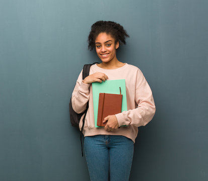 Young student black woman crossing arms, smiling and relaxed. She is holding books.