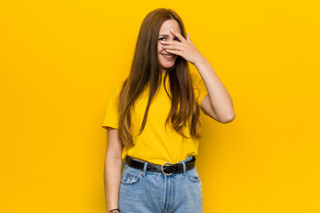 Young ginger redhead woman blink at the camera through fingers, embarrassed covering face. Wall mural