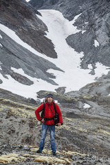 Young Caucasian man with backpack standing against snowy mountain pass, hiking
