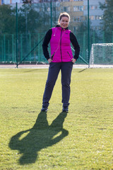 Attractive woman in sportswear standing on green pitch in the stadium, shadow from her body