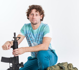 Curly haired man with rifle and backpack, isolated on white background