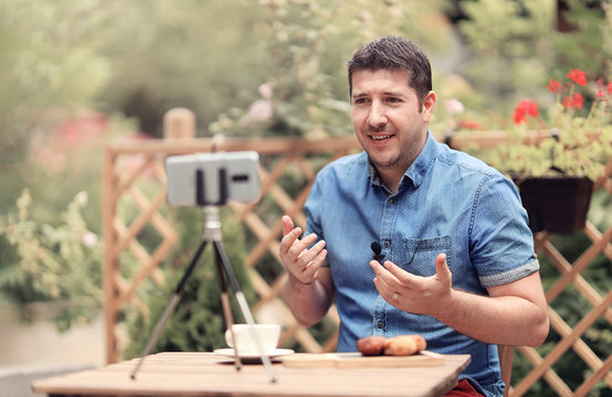 Man speaks in front of phone camera with and attached mic lavalier. Vlogger man sitting at a table and making a vlog episode. Man explaining and gesturing. Blogging (vlogging) and technology concept