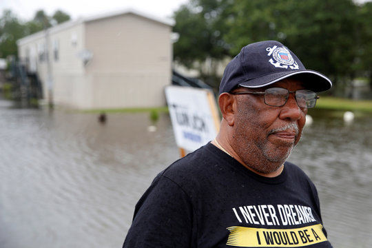 Eliot Sylve watches cars pass by during Hurricane Barry in Plaquemines Parish