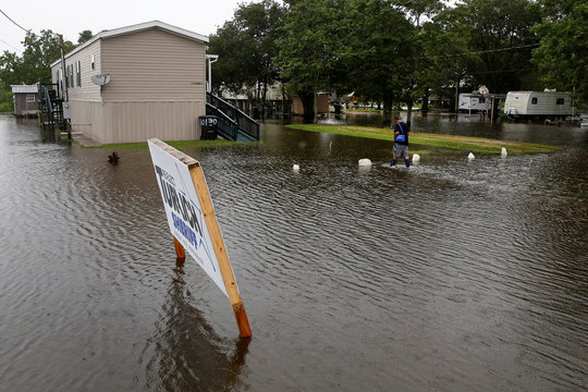 Eliot Sylve walks through flood waters back to his raised home during Hurricane Barry in Plaquemines Parish