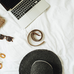 Women's fashion accessories, glasses, earrings, belt, straw hat, straw bag and laptop lying on bed...