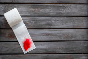 Proctology concept with toilet paper roll and red feather on wooden background top view mock-up