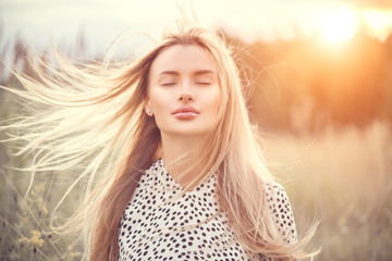 Portrait of beauty girl with fluttering white hair enjoying nature outdoors. Flying blonde hair on the wind. Beautiful young woman face closeup