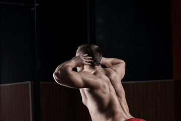 close up.rear view .a male bodybuilder performs an exercise