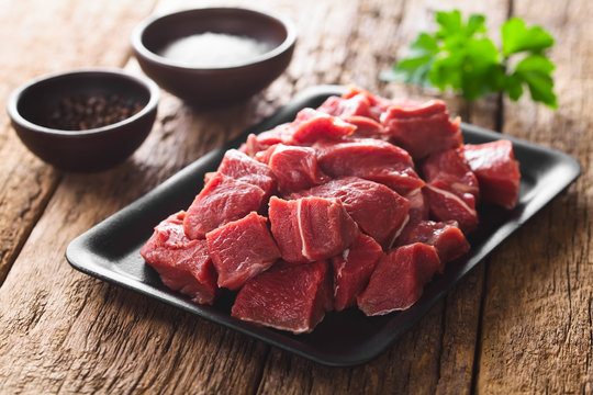 Fresh raw diced red beef meat on cast iron plate (Selective Focus, Focus one third into the meat)