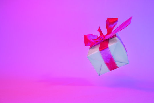 Gift box with red ribbon on trendy neon color background. zero gravity. levitation. copyspace. Concept sales, discount price, christmas presents and shopping