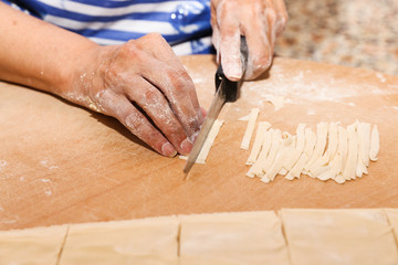 Side view woman's hands make Turkish Ravioli on table. Plates of traditional Turkish food. manti