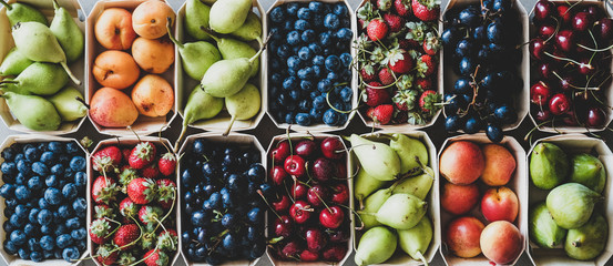 Summer fruit and berry variety. Flat-lay of ripe strawberries, cherries, grapes, blueberries, pears, apricots, figs in wooden eco-friendly boxes over grey background, top view