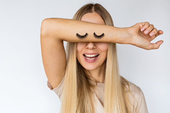 Funny young pretty woman with false eyelashes on her hand. Stylish female covering face with hand on white background. Concept of emotion, beauty, makeup and expression.