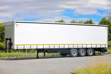 Semi remorque blanc triple essieux. Matériel de transport, remorques europe. Semi remorque européen stationné proche d'un dépôt de marchandises.