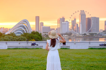 Wall Mural - Young Woman traveling with hat at Sunset, happy Asian traveler visit in Singapore city downtown. landmark and popular for tourist attractions. Asia Travel concept