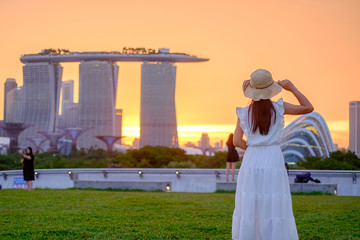 Fotobehang - Young Woman traveling with hat at Sunset, happy Asian traveler visit in Singapore city downtown. landmark and popular for tourist attractions. Asia Travel concept