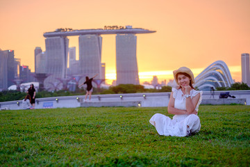 Fototapete - Young Woman traveling with hat at Sunset, happy Asian traveler visit in Singapore city downtown. landmark and popular for tourist attractions. Asia Travel concept
