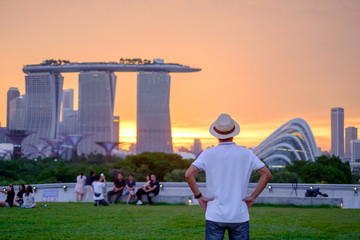 Fototapete - Young man traveling with hat at Sunset, solo Asian traveler visit in Singapore city downtown. landmark and popular for tourist attractions. Asia Travel concept