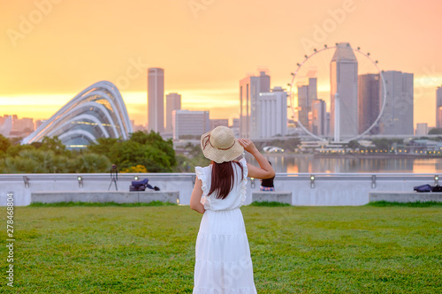 Fototapete Young Woman traveling with hat at Sunset, happy Asian traveler visit in Singapore city downtown. landmark and popular for tourist attractions. Asia Travel concept