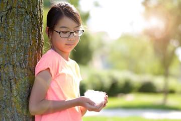 Asian teen girl leaning against tree in park against sunlight