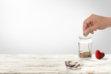 Hand of male insert coins in piggy bank saving money for health investment. Insurance policy to...